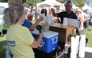 volunteers pouring beer at the cape may mac sip into spring festival