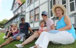 family sitting on a hill at the cape may mac sip into spring festival