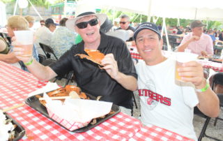 two guys drinking beer and eating crabs at the cape may mac Craft beer, Music & Crab Festival