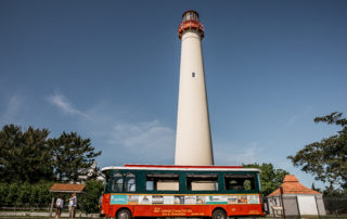 cape may lighthouse with the red and green trolley parked out front