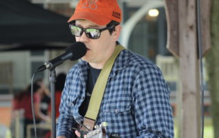 Michael Flanigan, musician, singing and playing guitar at the cape may mac sip into spring festival