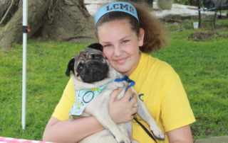 girl holding her pug at the cape may mac sip into spring festival