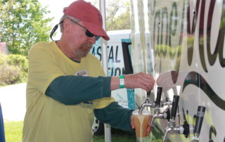 volunteer pouring beer at the cape may mac sip into spring festival