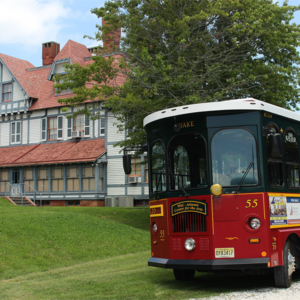 Cape May MAC's red and green trolley number 55 sitting outside of the Emlen PHysick Estate.