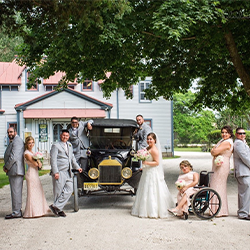 wedding party posing with emlen physicks model t car for a photo out side the carriage house on the grounds of emlen physick estate
