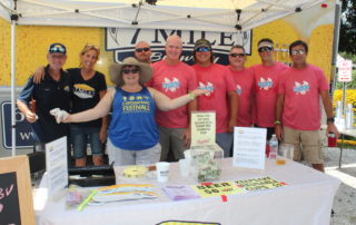 7 mile brewery staff and volunteers posing for photo at their booth at the cape may mac Craft beer, Music & Crab Festival