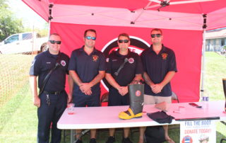 4 Firemen running a donation booth at the cape may mac Craft beer, Music & Crab Festival