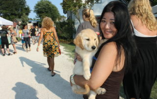 young woman holding her golden retriever puppy at the cape may mac Craft beer, Music & Crab Festival