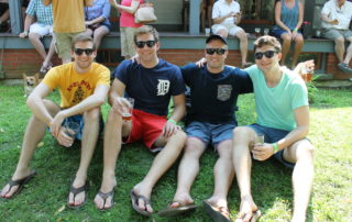 four guy friends sitting on a hill and drinking beer at the cape may mac Craft beer, Music & Crab Festival