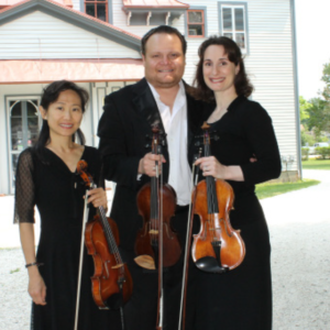 3 violinist standing outside of the carriage house on the emlen physick estate getting read to play a bach's lunch