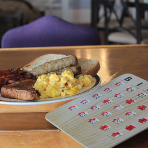 Scrambled eggs, sausage and toast plated on a table next to a bingo card for cape may macs Brunch & Bingo at the beach event.