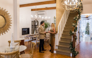 the owners of the Casblanca bed & breakfast talking to eachother inside their beautiful christmas decorated home