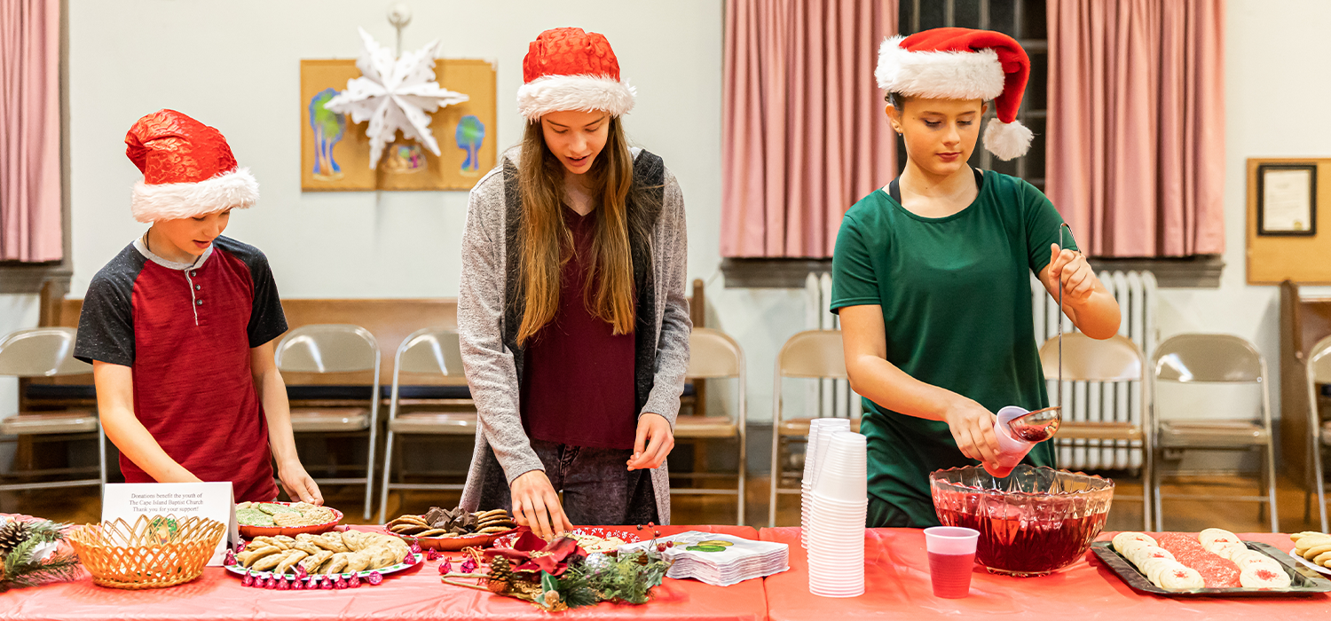 3 Young volunteers wearing santa hats serving cookies and juice in a hall for a holiday event
