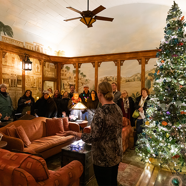 The owner of the mission inn is leading a christmas candlelight house tour in her living room with a beautiful Christmas tree lit up behind her