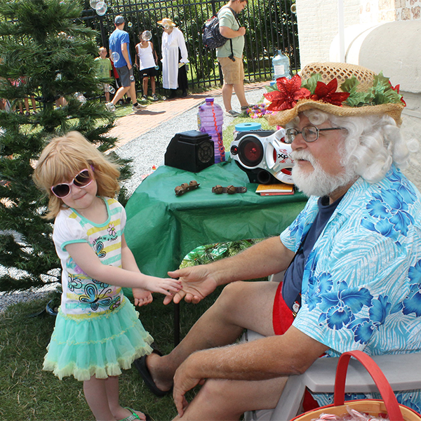 Little girl meeting santa dressed in summer clothes at a CHristmas in July event at the Cape May Lighthouse