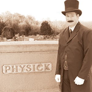 Doctor Emlen Physick dessed in a top hat and victorian coat stnading next to his gravestone that says Physick