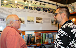 Lighthouse worker showing guest the panels detailing the history of the Cape May Lighthouse
