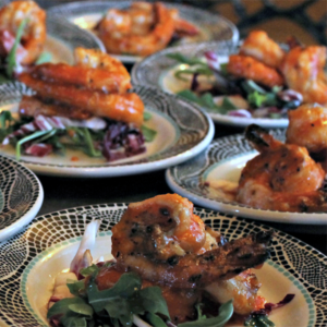 several plates of two grilled jumbo shrimp on top of salad elegantly plated