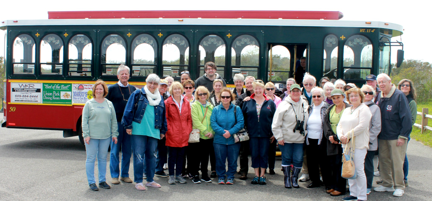Friends of the Lighthouse group taking a group photo with the red and green cape may mac trolley behind them.