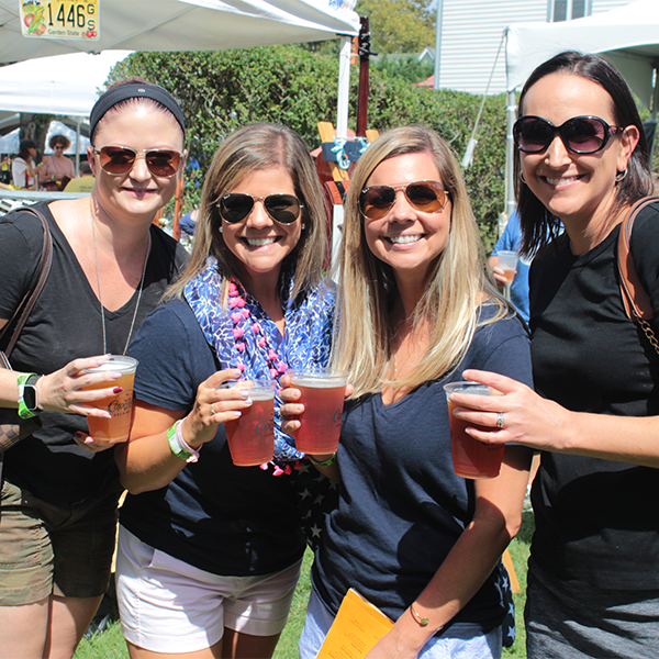 four women holding beer at the cape may mac harvest brew fest
