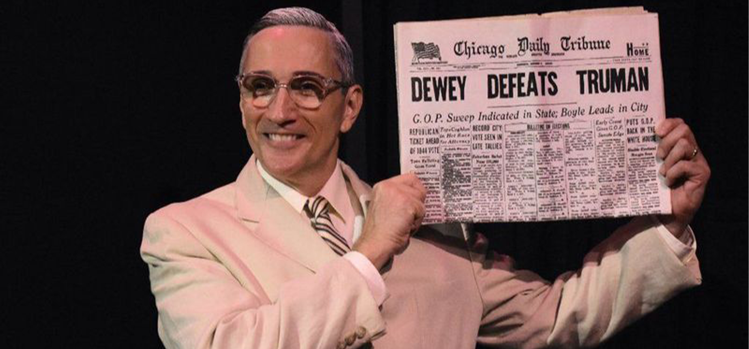 "An actor playing Harry S Truman holding a news paper that says ""Dewy Defeats Truman"""