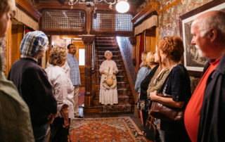 victorian dressed tour guide welcoming guests in the emlen physick estate