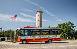 red and white trolley full of tourists stopping at the world war ii lookout tower in cape may new jeresey