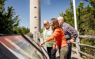 three people looking at informational panels outside the world war ii lookout tower in cape may new jesrey