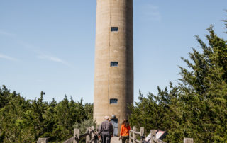 two people walking towards the entrance of the world war ii lookout tower in cape may new jersey