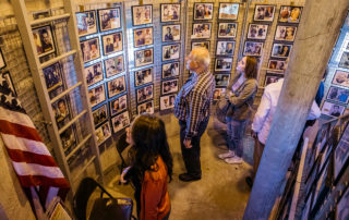 a group of people looking at photos in a world war ii veterans memorial museum inside the world war ii lookout tower in cape may new jersey