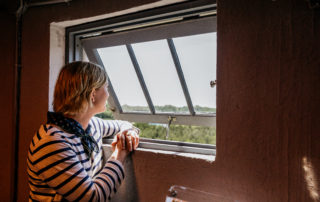 Woman inside the World War II Lookout Tower in Cape May, New Jersey, looking out a window at the beautiful view