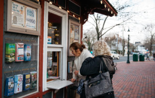 two women buying tickets at an information booth window in cape may new jersey