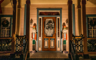 A Victorian front porch with 2 large nut crackers on either side of the door, a christmas wreath on the door, and a bright light lighting the front of the house