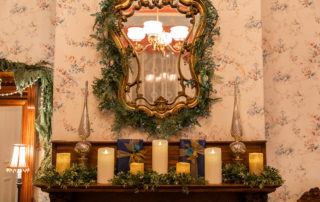 Candles and garland on a fireplace banister