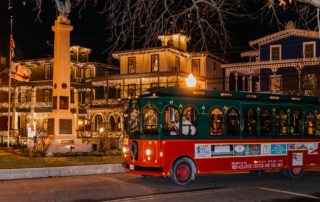 Cape May MAC Red and green trolley driving through the christmas lit streets of cape may new jersey