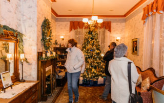 Small group of people looking around a living room decorated for christmas
