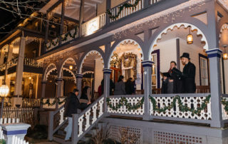 Carolers on the porch of a victorian Bed & Breakfast in cape may during the Christmas Candlelight House Tour