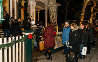 A group of women standing in line out side a property on tour for the christmas candlelight house tour