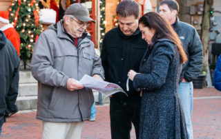 A Cape May MAC Employee helping two guests with the Christmas Candlelight House TOur Map