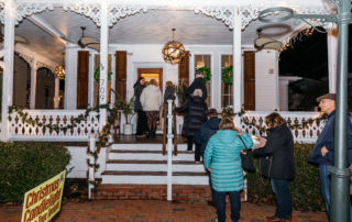 Group of tour goers entering a house on tour for the Christmas Candlelight House Tour in Cape May New jersey