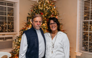 Husband and wife standing in the living room of their bed and breakfast that was on tour for the christmas candlelight house tour