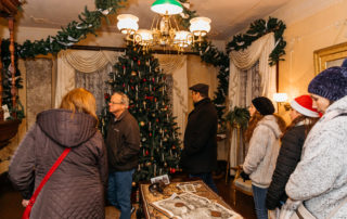 group of people looking around a christmas decorated living room of the emlen physick estate