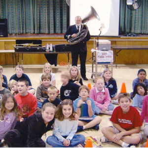 Man with trombone teaching children at an assembly about John Phillips Sousa