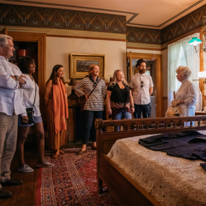 group touring a bedroom in the physick estate victorian house museum