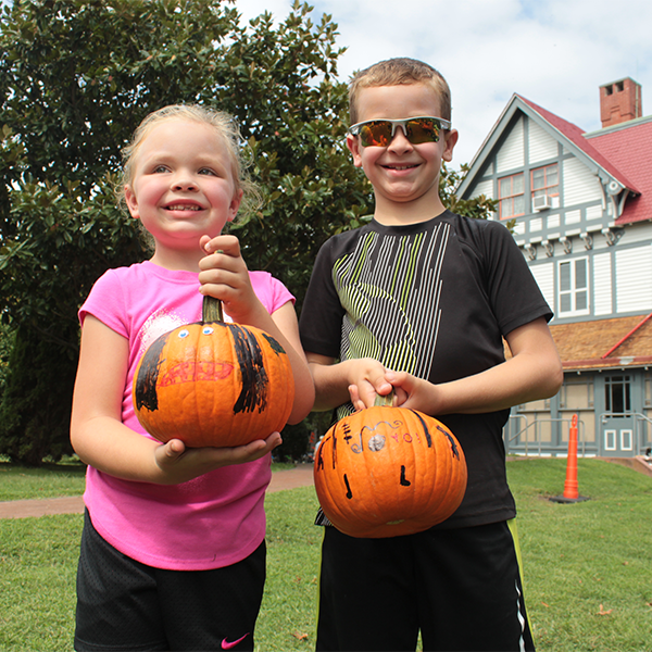 2 kids holding painted pumpkins that htye made at the crafts table at a cape may mac festival on the grounds of the physick estate