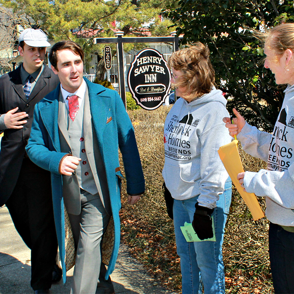 two actors dressed as sherlock holmes and dr watson walking the streets of cape may and passing sherlock holmes weekend participants looking for clues