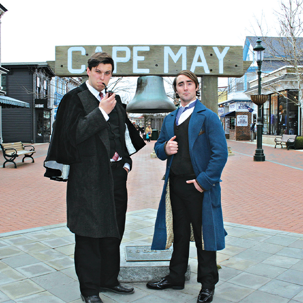 two guys dressed as sherlock holmes and watson standing in front of a the cape may sign on the Washington street mall