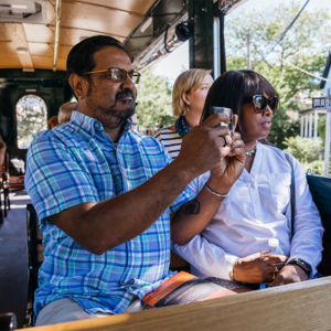 A couple sitting on a trolley tour taking photos