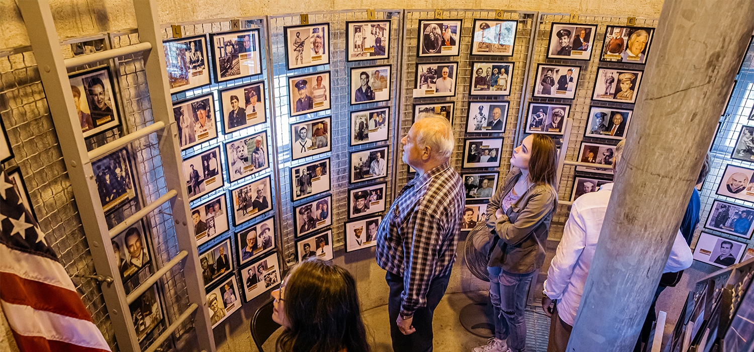 GROUP OF PEOPLE LOOK AT WALL OF PICTURES OF WWII VETERANS WHO HAVE DIED.
