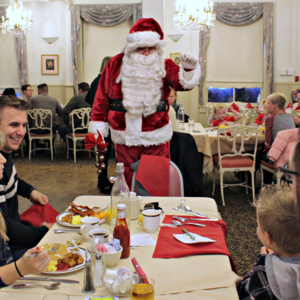 santa saying high to a child an his family eating breakfast